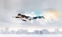 El vuelo del superhombre del héroe sobre ciudad con humo se fue detrás Imágenes de archivo libres de regalías