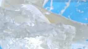 El vuelo salpica de la leche fresca que vierte en el aire en fondo azul en la cámara lenta en los fps 1500 almacen de metraje de vídeo