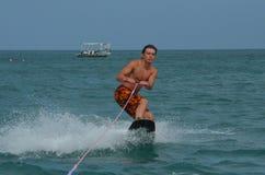 El Wakeboarder en un apretado se agacha de la costa de Aruba Imagen de archivo libre de regalías