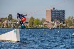El Wakeboarder está haciendo su truco en la pista de Wakeboard Imagen de archivo