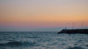 El waterscape de la tarde con el mar ondulado, el embarcadero rocoso y el vuelo gull almacen de video