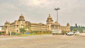 El wating de los vehículos del signl del tráfico delante de Vidhana Soudha el edificio de la legislatura estatal en Bangalore, la imagenes de archivo
