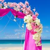 El Wedding en la playa Arco de la boda en púrpura adornado con flo Foto de archivo