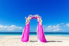 El Wedding en la playa Arco de la boda en púrpura adornado con flo Imagenes de archivo