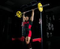 El weightlifter aumenta el barbell sobre su cabeza fotos de archivo