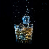 El whisky con el hielo que caía en el vidrio solated en negro Imagen de archivo