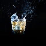 El whisky con el hielo que caía en el vidrio solated en negro Fotografía de archivo
