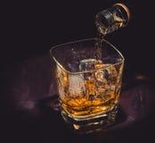 El whisky de colada del camarero en el vidrio en la tabla de madera, atmósfera caliente, viejo estilo occidental, época de se rel Foto de archivo
