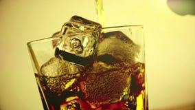 El whisky de colada del camarero en el vidrio con los cubos de hielo en el fondo de madera de la tabla, foco en los cubos de hiel almacen de video