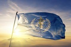 El WHO de la Organización Mundial de la Salud señala la tela del paño por medio de una bandera de la materia textil que agita en  fotografía de archivo