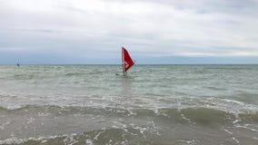 El Windsurfer en ondas del mar se cae al agua