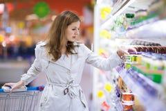 El womanshopping joven hermoso en supermercado Fotos de archivo libres de regalías