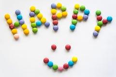 El ` y la sonrisa felices del ` de la palabra firman de las grageas coloreadas Fotografía de archivo
