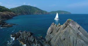 El yate, catamarán con las velas blancas flota hacia fuera de detrás un acantilado rocoso metrajes