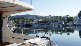 El yate costoso está en el puerto de una ciudad tropical Contra el contexto de palmeras, de casas blancas y de otras naves E almacen de metraje de vídeo