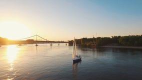 El yate de la navegación con las velas blancas nada a lo largo del río en la antena de la puesta del sol almacen de video