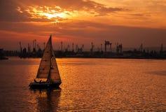 El yate de la navegación entra en el puerto de Varna en la puesta del sol Imagen de archivo libre de regalías