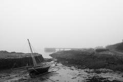 El yate en la playa como marea sale y una niebla de congelación viene adentro blA foto de archivo