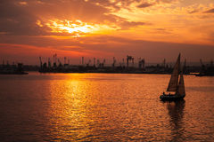 El yate entra en el puerto de Varna en la puesta del sol Foto de archivo