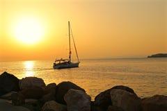 El yate flota en el mar del puerto deportivo en la puesta del sol Imagenes de archivo