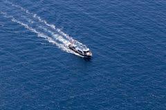 El yate navega en el agua azul hermosa cerca de la isla de Santorini, Foto de archivo libre de regalías