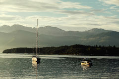 El yate y el barco de placer en la puesta del sol con las montañas en Kotor aúllan, M Imagen de archivo