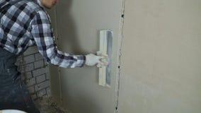 El yesero alisa el yeso humedecido en la pared interior con el espacio libre del cuchillo de masilla almacen de video
