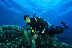 El zambullidor de equipo de submarinismo explora el filón coralino imagen de archivo libre de regalías