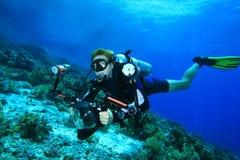 El zambullidor de equipo de submarinismo explora el filón coralino con su cámara foto de archivo libre de regalías