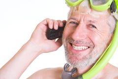 El zambullidor de piel sonriente tiene una llamada en su teléfono celular Imagenes de archivo