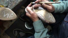 El zapatero en el trabajo El proceso de reparar los zapatos en taller almacen de metraje de vídeo