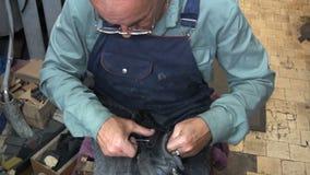 El zapatero en el trabajo El proceso de reparar los zapatos en taller almacen de video