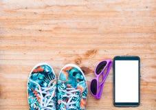 el zapato de lona con las gafas de sol y el teléfono móvil en backg de madera Imagen de archivo