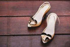 El zapato de marfil de la bomba del ` s de las mujeres adornó con el corazón del cepillo en el piso de madera con el espacio, pri Imagen de archivo