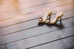 El zapato de marfil de la bomba de las mujeres adornó con el corazón del cepillo en el piso de madera con el espacio Fotografía de archivo