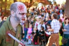 El zombi masculino con la herida de puñalada recorre en el desfile de Halloween Imagen de archivo
