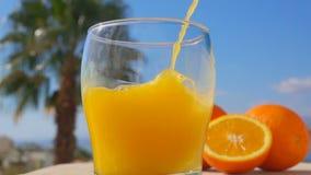 El zumo de naranja del primer vertió en un vidrio almacen de video