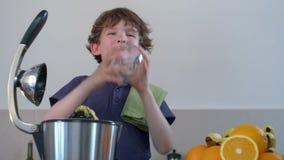 El zumo de naranja fresco hecho en casa del muchacho caucásico divertido joven en cocina con el Juicer eléctrico y lo bebe metrajes