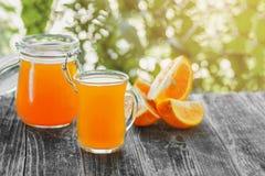El zumo de naranja recientemente exprimido en un vidrio con las rebanadas de lirios anaranjados y amarillos florece en el fondo v Imagen de archivo libre de regalías