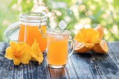El zumo de naranja recientemente exprimido en un vidrio con las rebanadas de lirios anaranjados y amarillos florece en el fondo v Foto de archivo libre de regalías