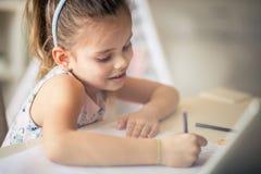 Ela ` s um estudante diligente na escola e em casa foto de stock