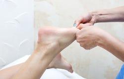 Elabora il massaggio del piede Fotografie Stock