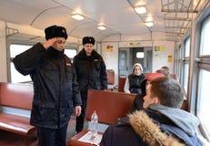 Elaboración de los oficiales de policía de la supresión de la violación del orden público en el coche de un tren eléctrico Fotos de archivo libres de regalías