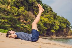 Elaboración masculina joven en la playa, hombre deportivo que hace ejercicios fotografía de archivo