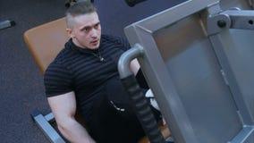 Elaboración masculina joven en un gimnasio y hacer ejercicios de pierna almacen de metraje de vídeo