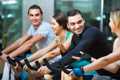 Elaboración sonriente del grupo del ciclo en club de fitness Fotografía de archivo