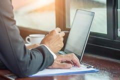 Elaborando en el ordenador portátil, cierre de manos del hombre de negocios imagen de archivo