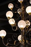Elaborate chandelier hangs from a roof with art deco decorations and round glass spheres royalty free stock images