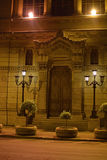 Elaborate doorway in Rome, Italy. A wooden doorway set between elaborate stonework and decorative streetlamps Stock Images