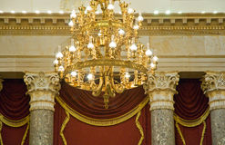 Elaborate gold chandelier. A view of a huge, gold chandelier in a rich, luxurious mansion chamber. Slight lens flare stock photography
